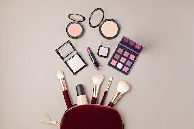 Leżał z zestawem profesjonalnych kosmetyków dekoracyjnych, narzędzi do makijażu i akcesoriów dla kobiet na szarej ścianie z miejscem na kopię. blog uroda, moda, impreza i koncepcja zakupów. widok z góry