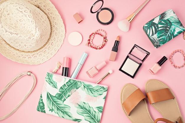 Leżał z zestawem profesjonalnych kosmetyków dekoracyjnych, narzędzi do makijażu i wiosennych akcesoriów dla kobiet, letnich na różowej ścianie z miejscem na kopię. blog uroda, moda, impreza, koncepcja zakupów. widok z góry