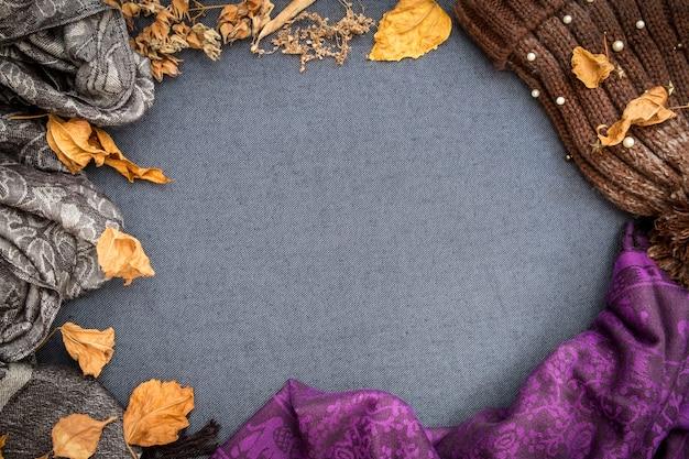 Leżała jesień zima. brązowa dzianinowa czapka, fioletowy szalik i suche liście na niebiesko