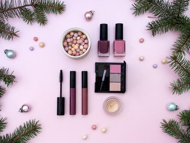 Leżała kompozycja z kosmetykami do makijażu i świątecznym wystrojem na różowym tle. widok z góry. banner piękna na sprzedaż
