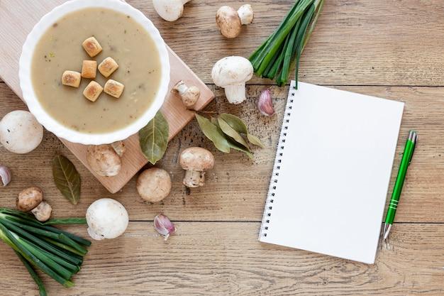 Leżała na płasko domowa zupa grzybowa i notatnik