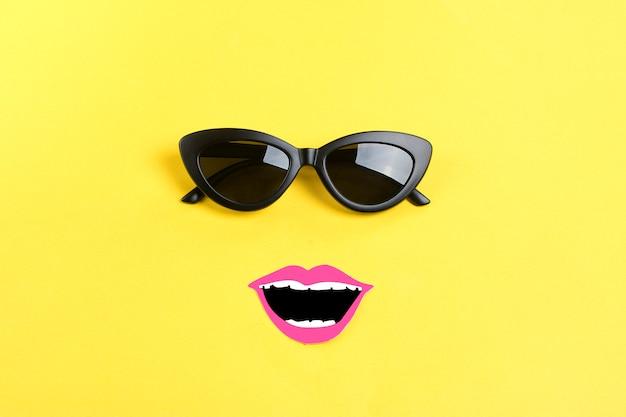 Leżało słońce ze stylowymi czarnymi okularami przeciwsłonecznymi, uśmiechnięte usta na żółtym flat