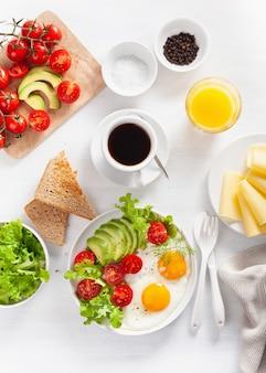 Leżało zdrowe śniadanie. jajka sadzone, awokado, pomidor, tosty i kawa