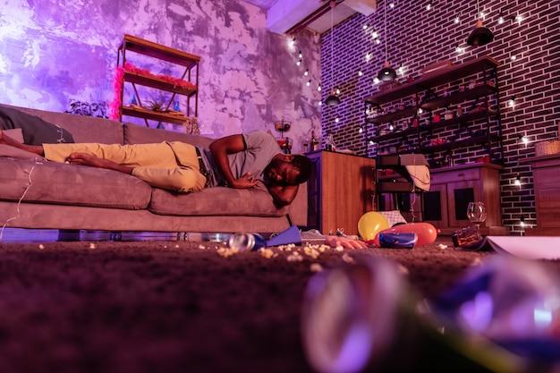 Leżenie bez ruchu. szkoda człowieka w beżowych spodniach, który przetrwał wczorajsze konsekwencje podczas szalonej domowej imprezy