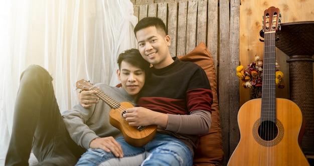 Lgbt męski homoseksualista dobrze się bawi grający na gitarze razem.