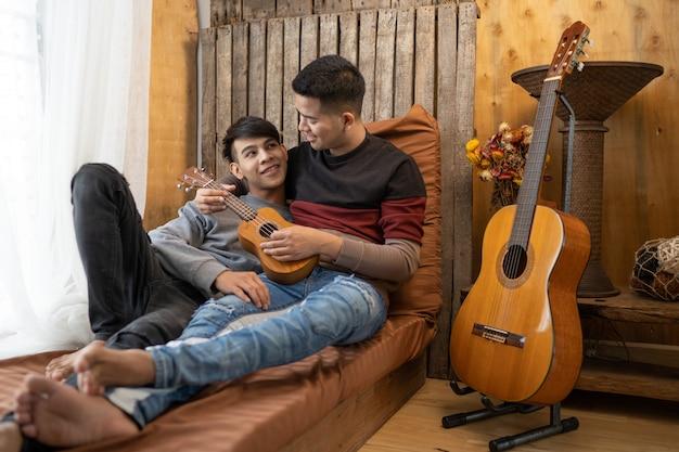 Lgbt mężczyzna homoseksualista bawiący się razem w grę na gitarze.