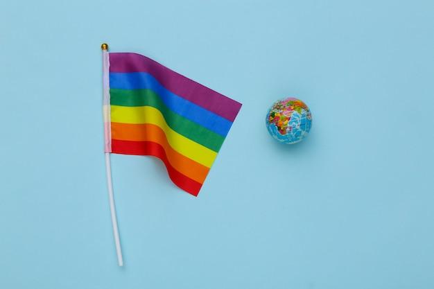 Lgbt tęczowa flaga i kula ziemska na niebieskim tle. tolerancja, wolność