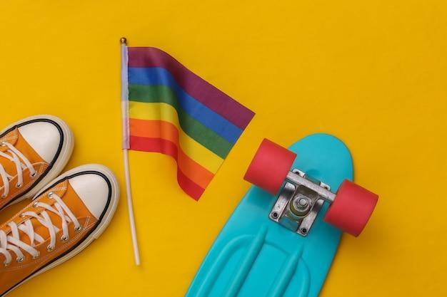 Lgbt tęczowa flaga i trampki, deska cruiser na żółtym tle. tolerancja, wolność, parada gejów