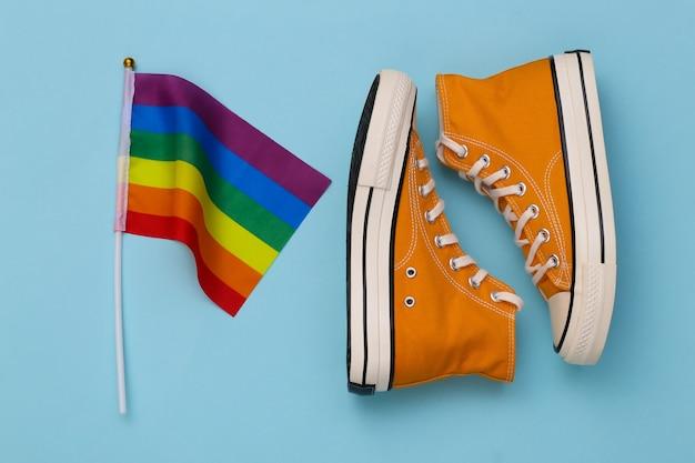 Lgbt tęczowa flaga i trampki na niebieskim tle. tolerancja, wolność, parada gejów