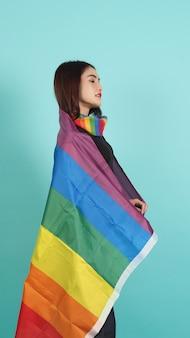 Lgbtq dziewczyna i flaga dumy. seksowna dziewczyna lesbijek i stojąca flaga lgbt. niebieskie zielone tło.