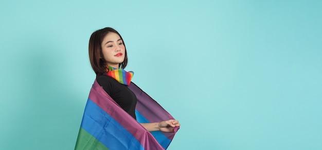 Lgbtq dziewczyna i flaga dumy. seksowna dziewczyna lesbijek i stojąca flaga lgbtq. niebieskie zielone tło.