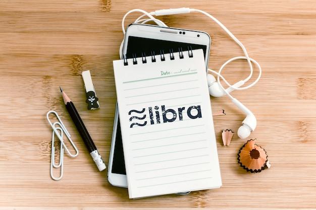 Libra kryptowaluta i symbol łańcucha blokowego w notatniku ołówkiem i smartfonem na drewnianym stole, nowa cyfrowa waluta