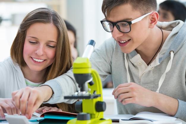 Licealiści. dziewczyna i chłopak pracuje razem w biologii w klasie