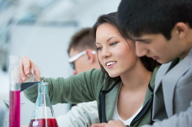 Licealiści. grupa studentów pracujących w klasie chemii: mieszanie płynnych odczynników i używanie szklanych naczyń