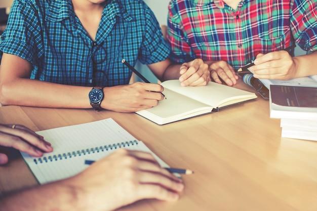 Licealiści lub studenci studiujący i czytający razem w bibliotece