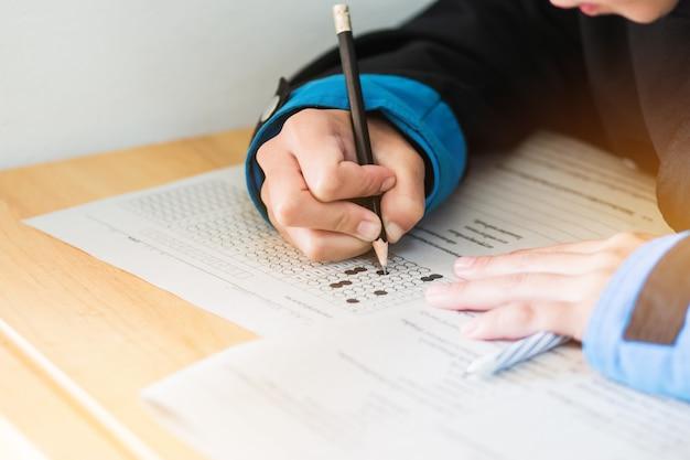 Liceum lub student uniwersytetu ręce biorąc egzaminy
