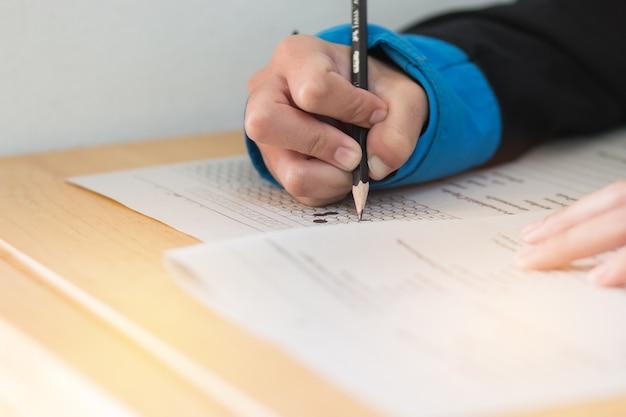 Liceum lub studentka ręce biorąc egzaminy, egzamin pisemny