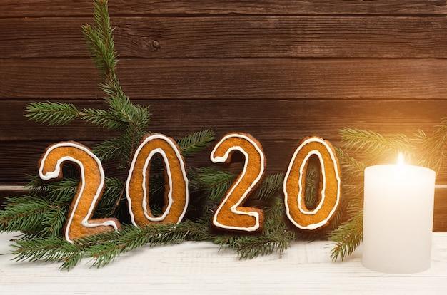 Liczba 2020 z piernikowych ciasteczek na. świerkowe gałęzie i świeca. koncepcja bożego narodzenia