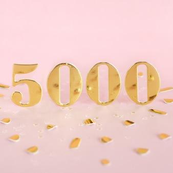 Liczba 5000 w banerach złotych liczb i złotych konfetti.