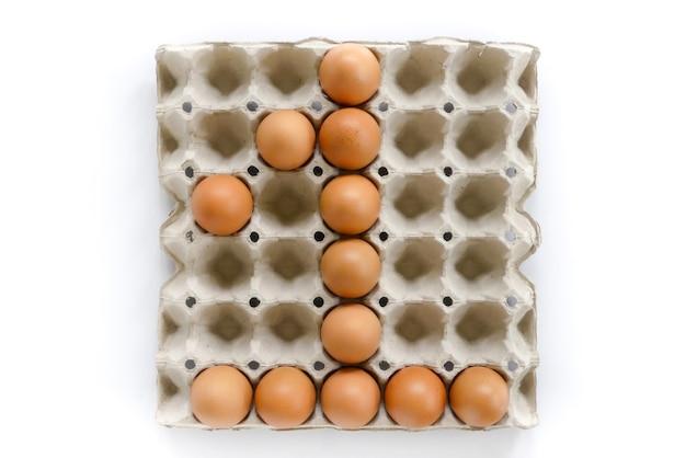 Liczba listy układają od jajek w papierowej tacy na białym tle.