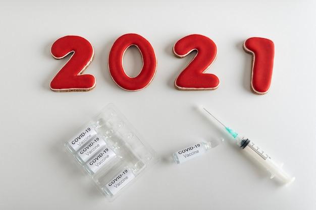Liczby 2021 ampułka ze szczepionką covid-19 i strzykawką na białym tle.