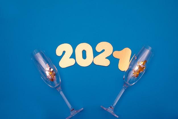 Liczby 2021 na niebieskim tle z kieliszkami szampana i cukierków