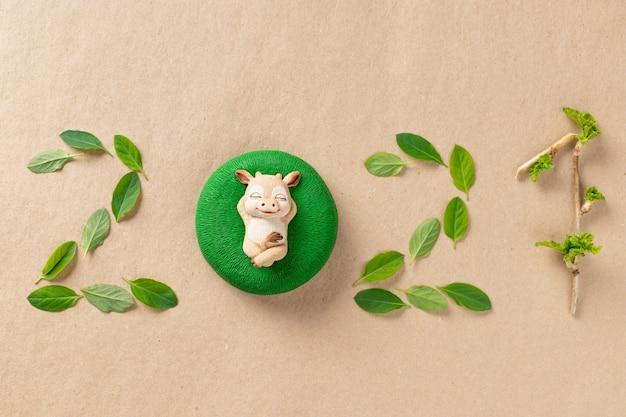 Liczby 2021 wykonane z zielonych liści i symbolu świątecznego byka