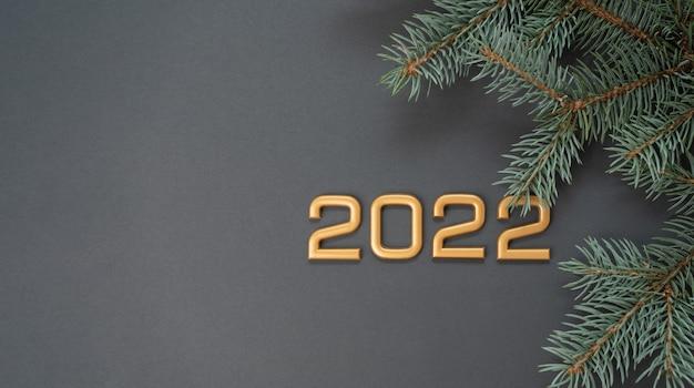 Liczby 2022 na szarym tle z gałązką świerkową. koncepcja nowego roku i bożego narodzenia.