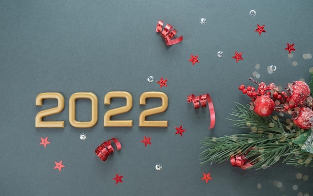 Liczby 2022 na szarym tle z ozdobami świątecznymi konfetti bokeh