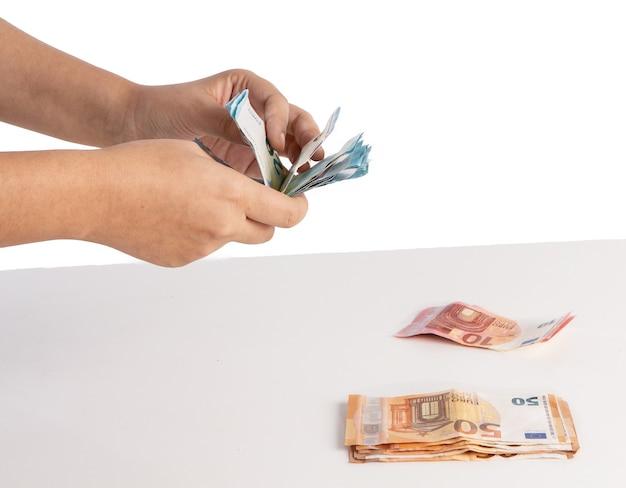 Liczenie banknotów euro na stole na białym tle