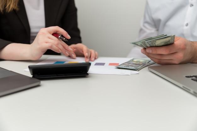 Liczenie pieniędzy w biurze. konto profesjonalne na laptopie i kalkulatorze.
