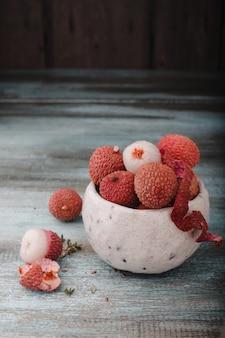 Liczi chinensis z miejsca kopiowania. świeże liczi owoc w pucharze w starym nieociosanym woodenwall. surowy czerwony organicznie liczi owocowy przygotowywający jeść.