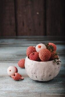 Liczi chinensis z miejsca kopiowania. świeże owoce liczi w misce w starym rustykalnym drewnianym stole. surowy czerwony organicznie liczi owocowy przygotowywający jeść.