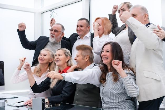 Liczne grono zadowolonych pracowników pokazujących swoje sukcesy