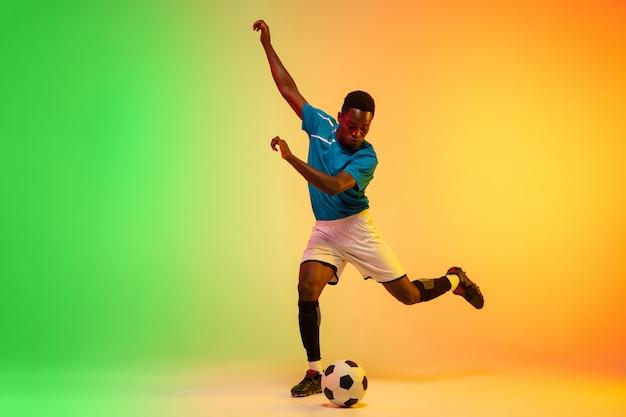 Lider afroamerykański piłkarz trenujący w akcji na gradiencie