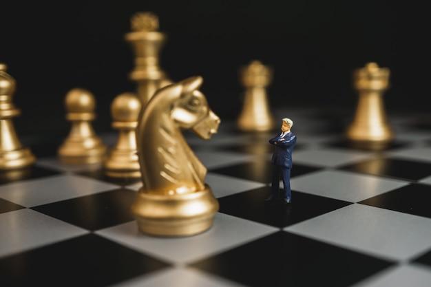 Lider biznesmen stoi z ufnością przed szachowymi końmi.