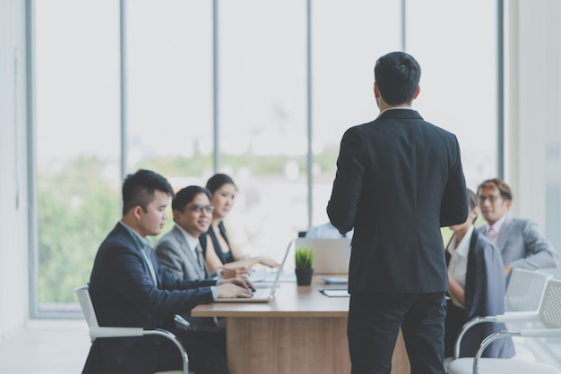 Lider biznesmena przedstawia do pracy podczas spotkania z kolegami w biurze. prezentacja spotkania zespołu biznesowe, planowanie biznesowe koncepcja konferencji