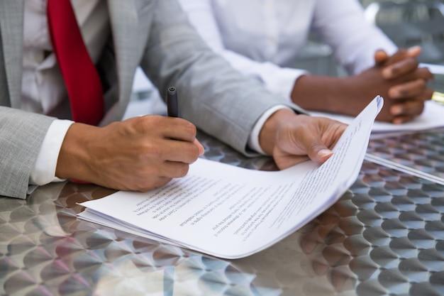 Lider biznesu czyta tekst umowy i sprawdza