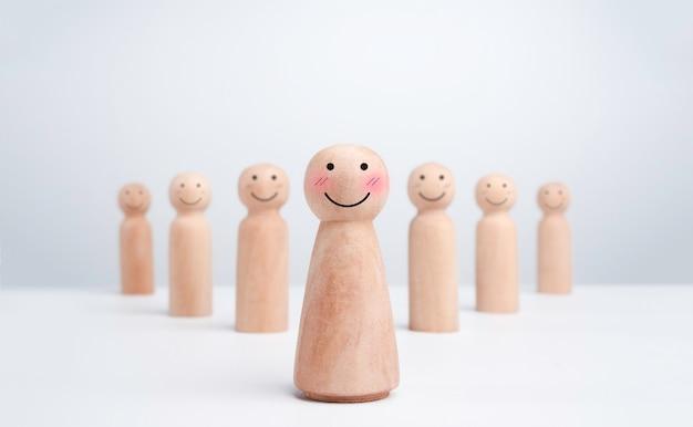 Lider dziewczyna, influencer, drewniana figura, uśmiechnięta z uroczą buzią emotikon stojącą przed szczęśliwymi dziećmi na białym tle, minimalistyczny styl. przywództwo, upodmiotowienie i koncepcja zwycięzcy.