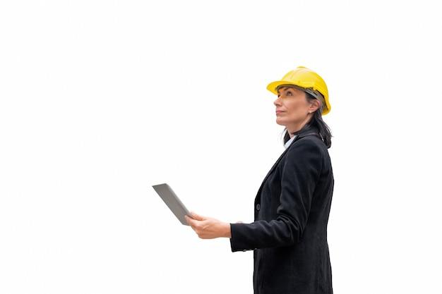 Lider kobieta inżynier z kasku stojaka trzymając laptopa na białym tle