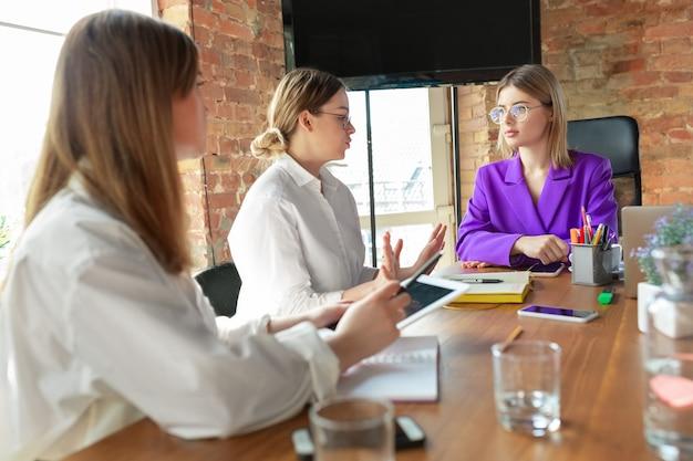 Lider. młoda biznesowa kaukaski kobieta w nowoczesnym biurze z zespołem. spotkanie, dawanie zadań. kobiety pracujące w biurze.