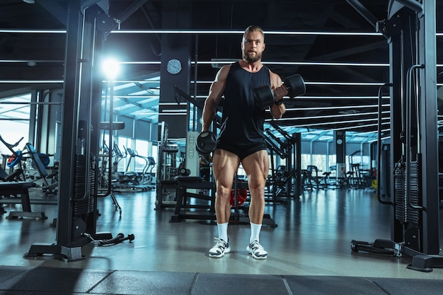 Lider. młody muskularny kaukaski sportowiec trenuje na siłowni, robi ćwiczenia siłowe, ćwiczy, pracuje nad górną częścią ciała z ciężarkami i sztangą. fitness, wellness, koncepcja zdrowego stylu życia.
