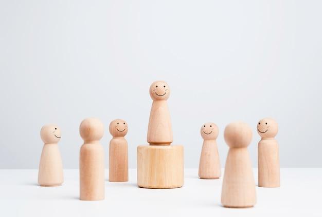 Liderka, influencerka, drewniana figura, uśmiechnięta kobieta stojąca na pudle otaczającym szczęśliwymi ludźmi na białym tle, styl minimalistyczny. przywództwo, upodmiotowienie i koncepcja zwycięzcy.