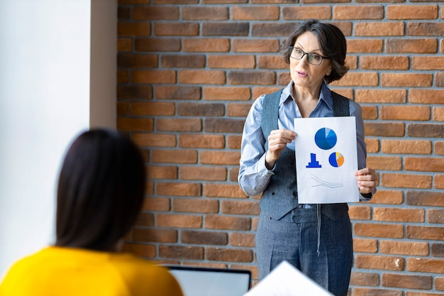 Liderka mentorki w podeszłym wieku, która uczy pracownika analizowania sprzedaży lub wyjaśnia nową strategię biznesową na spotkaniu w biurze