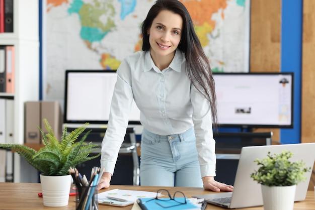 Liderka stoi z rękami na stole w swoim biurze