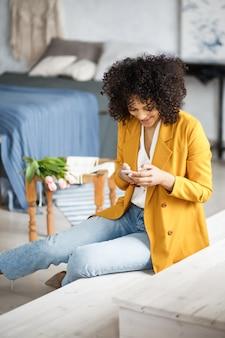 Lifestyle concept - portret pięknej kobiety afroamerykanów radosnego słuchania muzyki na telefonie komórkowym. żółte pastelowe studio tło. kopiuj przestrzeń.
