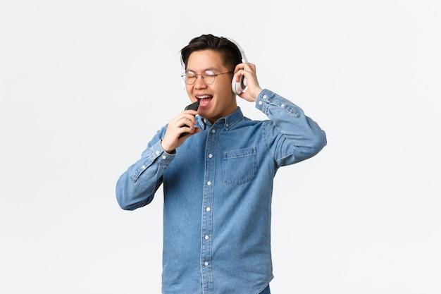 Lifestyle koncepcja wypoczynku i technologii beztroski szczęśliwy azjatycki młody człowiek grający w aplikację karaoke za pomocą wi...