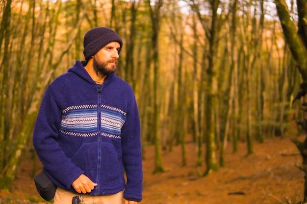 Lifestyle, młody człowiek w niebieskim wełnianym swetrze i kapeluszu, ciesząc się jesienią w lesie. las artikutza w san sebastin, gipuzkoa, kraj basków. hiszpania