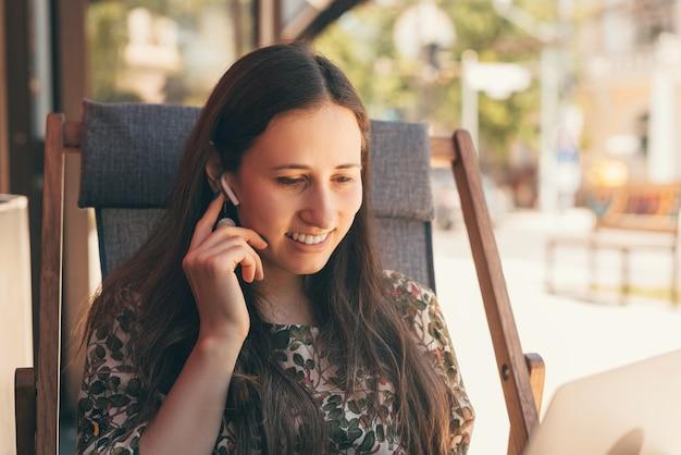 Lifestyle zdjęcie młodej kobiety siedzącej na krześle łączącym jej strąki do uszu.