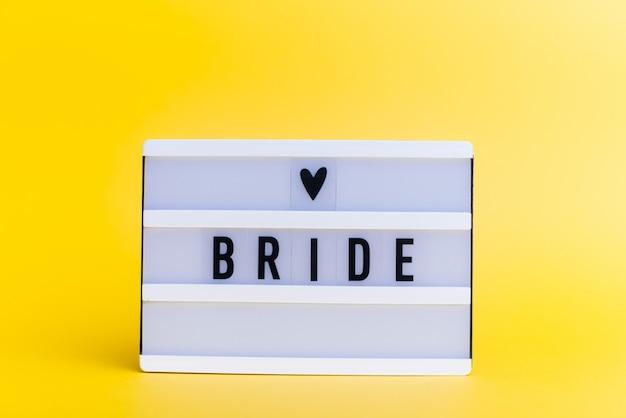 Light box z tekstem, bride, na żółtej ścianie